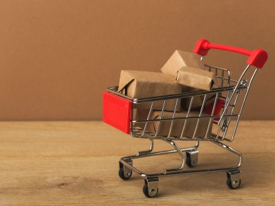 Miniature shopping cart and parcels on brown background,